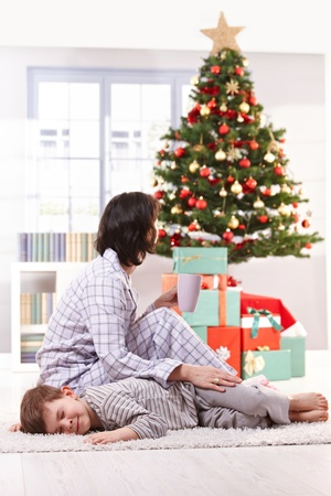 Mother and son in pyjama on christmas morning, little boy asleep on carpet, woman having coffee. Stock Photo - 10533291