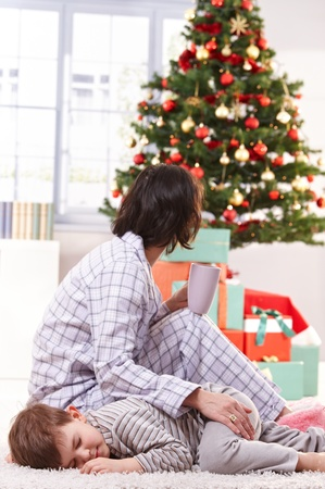 tired eyes: Mother stroking sleeping son on christmas morning, looking at tree and wrapped gifts, having tea.