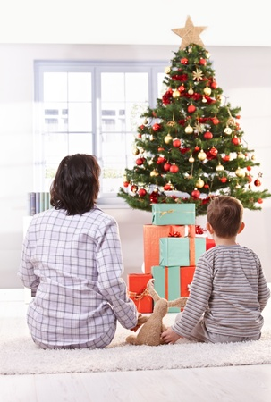 Mom and son sitting together, holding hands with toy, looking at christmas tree and presents on christmas morning. photo