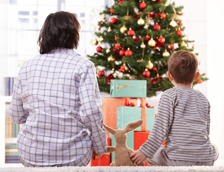 Mother, toy and son on christmas morning sitting together on floor waiting to open christmas gifts. Stock Photo - 10533311