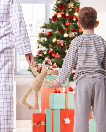 christmas morning: Mother and son both in pyjama holding toy bunny looking at tree and christmas gifts in morning.