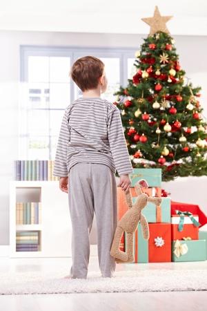 Pyjama chłopiec gospodarstwa zabawki króliczek patrząc na choinkę i prezenty w godzinach porannych.
