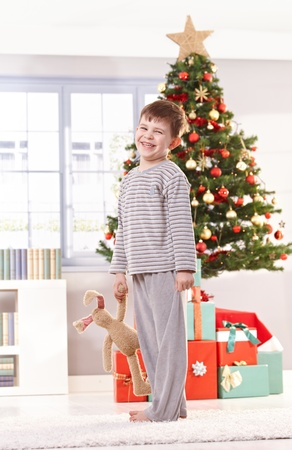 Happy little boy wearing pyjama, holding toy bunny, standing at christmas tree waiting for presents, laughing at camera. photo