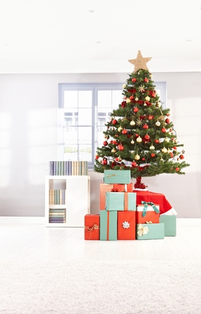 home decorated: Decorated christmas tree and wrapped gifts at home in morning light.