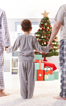 christmas morning: Family standing in pyjama holding hands on christmas morning.
