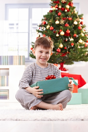 indoor photo: Laughing boy sitting on floor with wrapped christmas present in morning light.