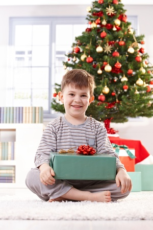 Portrait of happy little kid sitting in pyjama in christmas morning holding gift parcel, smiling at camera. photo