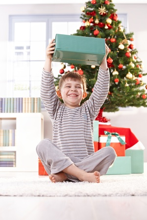 Small boy laughing, sitting on floor in morning, holding up christmas present happily. Stock Photo
