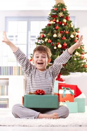 arms wide: Felice ragazzino in pigiama ottenere presente a Natale, ridendo a porte chiuse con le braccia aperte.