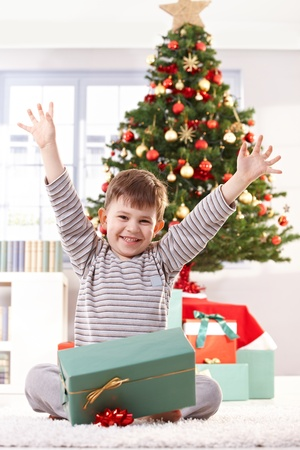 '5 december': Happy kid sitting in pyjama on christmas morning, raising arms, getting christmas gift, laughing at camera. Stock Photo