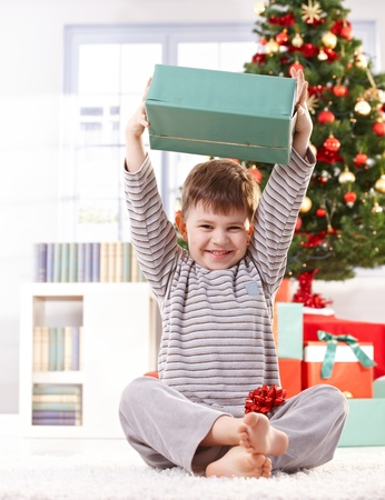 Cute kid sitting in pyjama on floor on christmas morning, raising wrapped christmas gift parcel high, laughing. Stock Photo