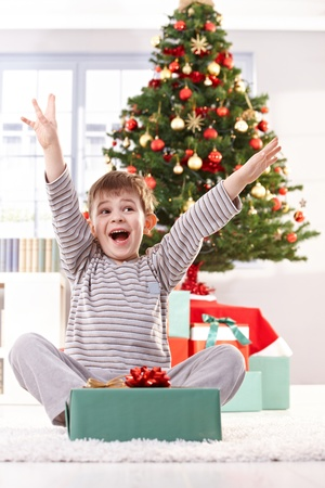 '5 december': Kid yelling happily at christmas gift with arms raised, sitting at christmas tree in morning.