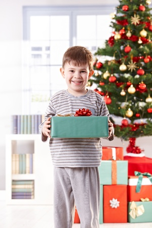 christmas morning: Happy little boy standing with christmas present in hand in morning light, smiling at camera.