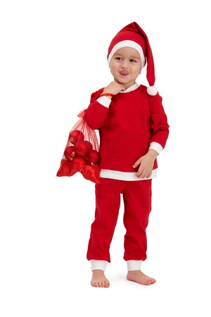 1 boy only: Cute kid grimacing in santa costume, sticking tongue, holding red bag. Stock Photo