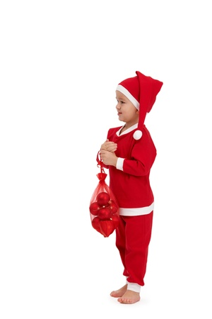 three people only: Cute kid dressed as santa, holding bag full of christmas bulb. Stock Photo