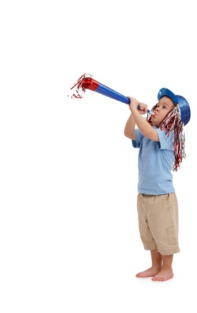 new year party: Happy little kid with party horn, wearing decorated hat. Stock Photo