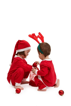 Small children in santa costume playing with christmas tree decoration. Stock Photo - 10663521