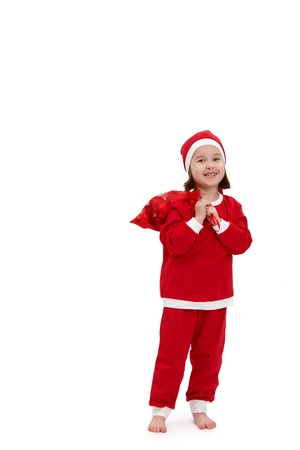 Small happy girl in santa costume, holding christmas bulb in bag, smiling at camera. Stock Photo - 10663484