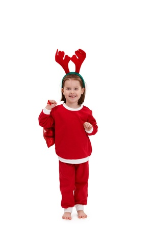 Happy little girl in santa costume wearing funny reindeer hair band holding red bag. photo