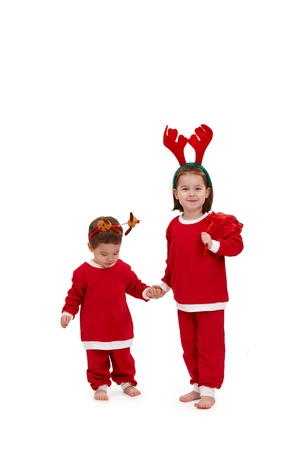 Cute kids wearing santa costume, standing holding hands. photo
