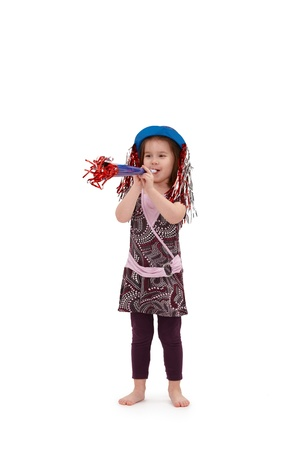 image size: Cute little girl dressed for birthday, having party accessories, blowing horn.