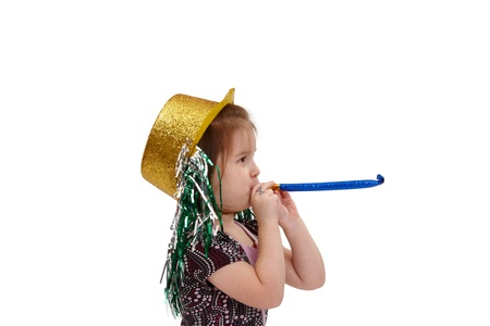 have on: Small girl wearing party hat, using horn at new year celebration.