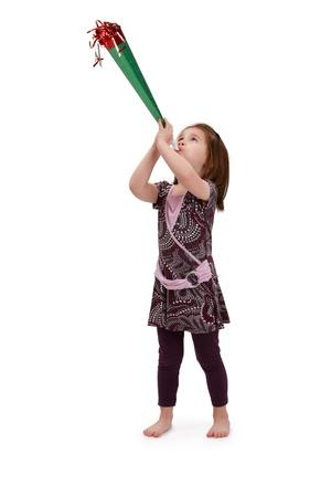 joyous: Little girl in cute pretty dress blowing party horn, celebrating.