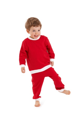 1 2 years: Happy little boy in santa costume laughing, standing on one foot.