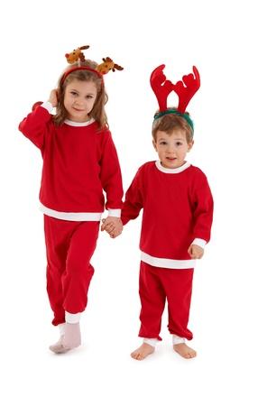 christmas costume: Christmas portrait of cute siblings wearing reindeer hair band and santa costume, holding hands.