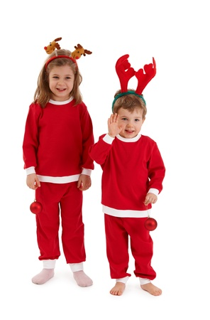 full size: Laughing children in reindeer hair band and santa costume standing together, having christmas bulb, little boy waving.