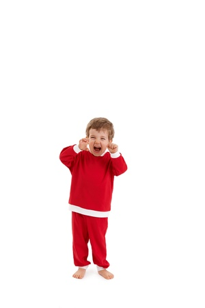 Little boy in santa costume yelling, raising fist, having fun. photo