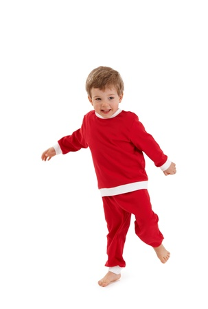 Portrait of laughing little boy in santa costume standing on one foot. photo