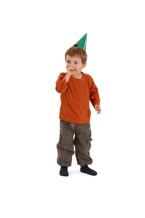 boys only: Small boy in party hat, laughing, with hand at mouth.