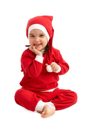 Portrait of happy little girl in santa costume and hat, laughing at camera.
