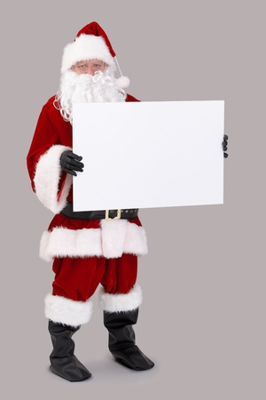Full size portrait of Santa holding blank white board, looking at camera, isolated on gray background. photo