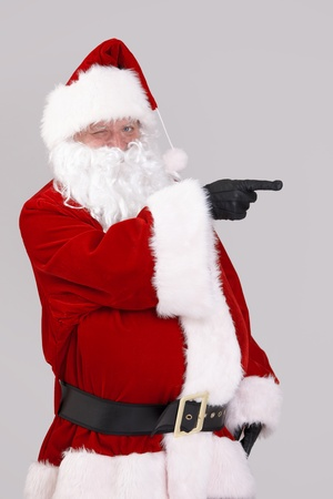 Portrait of Santa Claus pointing to blank space, looking at camera, isolated on gray background. photo