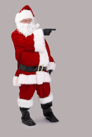 Full size portrait of Santa Claus pointing to blank space, isolated on gray background. photo