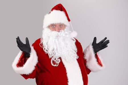 Portrait of surprised Santa Claus, looking at camera, isolated on gray background. photo