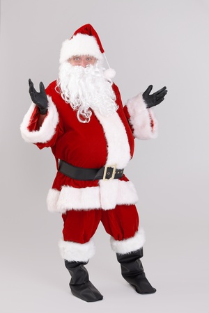 Full size portrait of surprised Santa Claus looking at camera, isolated on gray background. Stock Photo