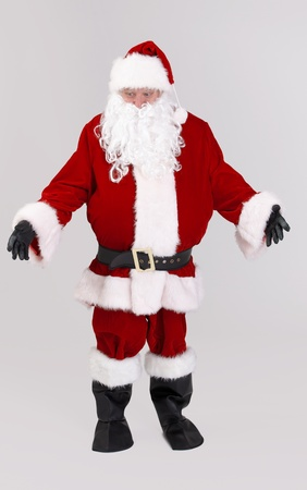 outspreading: Full size portrait of Santa outspreading arms, looking down, isolated on gray background. Stock Photo