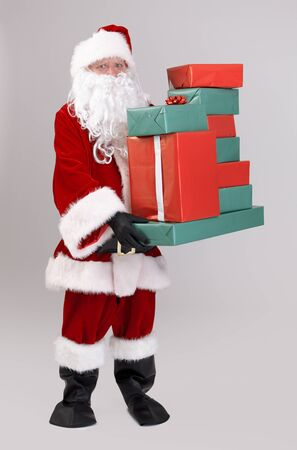 box size: Full size portrait of Santa lifting christmas presents, looking at camera, isolated on gray background. Stock Photo
