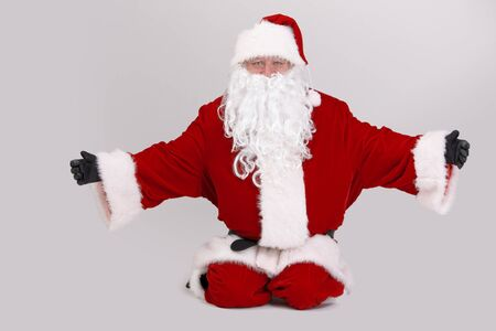 outspreading: Full size portrait of Santa kneeling on ground outspreading arms, looking at camera, isolated on gray background.
