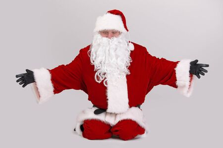 outspreading: Full size portrait of Santa kneeling on ground outspreading arms, looking down, isolated on gray background. Stock Photo