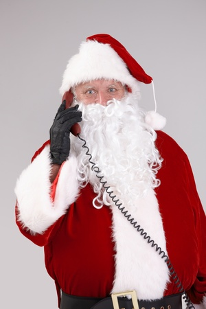 portrait of santa talking on phone looking at camera, looking at camera, isolated on gray background.� Stock Photo - 10663547
