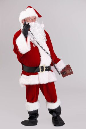 full size portrait of santa talking on phone, looking away, isolated on gray background.� Stock Photo