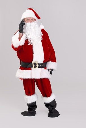 full size portrait of santa talking on mobile phone, looking at camera, isolated on gray background.� photo