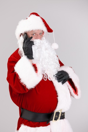 portrait of santa talking on mobile looking at camera, isolated on gray background.� photo