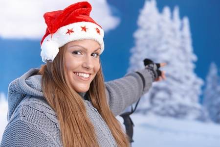 looking after: attractive girl in santa hat, dressed up warm, pointing to winter landscape, smiling.�