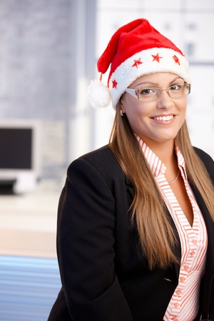 portrait of young woman wearing santa claus hat in office, smiling.� Stock Photo - 10663558