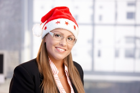 portrait of attractive female wearing santa claus hat in office, smiling.� Stock Photo - 10663554